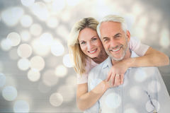 Composite image of smiling couple embracing and looking at camera Stock Photo