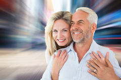 Composite image of smiling couple embracing with woman looking at camera. Smiling couple embracing with women looking at camera against blurry new york street Royalty Free Stock Image