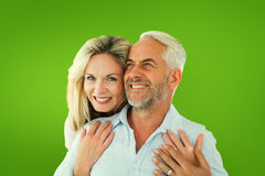Composite image of smiling couple embracing with woman looking at camera. Smiling couple embracing with women looking at camera against green vignette Stock Photos