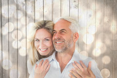 Composite image of smiling couple embracing with woman looking at camera Stock Images