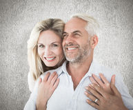 Composite image of smiling couple embracing with woman looking at camera. Smiling couple embracing with women looking at camera against weathered surface Stock Photography