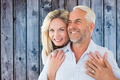 Composite image of smiling couple embracing with woman looking at camera Stock Image