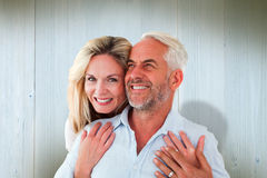 Composite image of smiling couple embracing with woman looking at camera Royalty Free Stock Photography