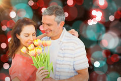 Composite image of smiling couple with flowers bouquet Royalty Free Stock Image