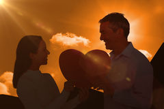 Composite image of smiling couple holding heart shape paper. Smiling couple holding heart shape paper against a cloudy sky Royalty Free Stock Photos