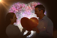 Composite image of smiling couple holding heart shape paper. Smiling couple holding heart shape paper against colourful fireworks exploding on black background Royalty Free Stock Image
