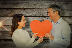 Composite image of smiling couple holding heart shape paper. Smiling couple holding heart shape paper against digitally generated grey wooden planks Royalty Free Stock Photo