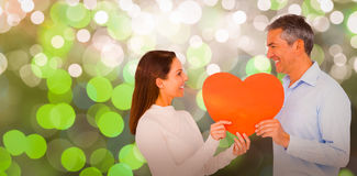 Composite image of smiling couple holding heart shape paper. Smiling couple holding heart shape paper against glowing background Royalty Free Stock Photo