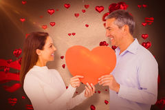 Composite image of smiling couple holding heart shape paper. Smiling couple holding heart shape paper against love heart pattern Royalty Free Stock Images