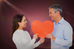 Composite image of smiling couple holding heart shape paper. Smiling couple holding heart shape paper against red vignette Royalty Free Stock Photography