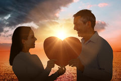 Composite image of smiling couple holding heart shape paper. Smiling couple holding heart shape paper against sunrise over field Royalty Free Stock Images