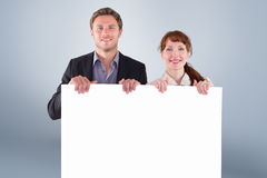 Composite image of smiling couple holding large sign Royalty Free Stock Photo