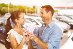 Composite image of smiling couple holding money Royalty Free Stock Photo
