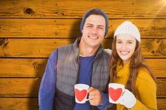 Composite image of smiling couple holding mug Royalty Free Stock Photography