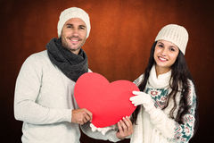 Composite image of smiling couple holding paper heart. Smiling couple holding paper heart against shades of brown Royalty Free Stock Images