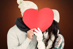 Composite image of smiling couple holding paper heart. Smiling couple holding paper heart against shades of brown Royalty Free Stock Image