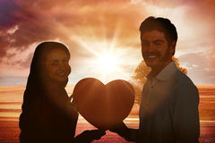 Composite image of smiling couple holding paper heart Royalty Free Stock Image