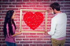 Composite image of smiling couple holding picture frame Royalty Free Stock Photo