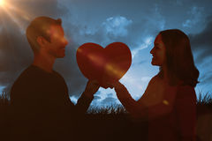 Composite image of smiling couple holding red heart shape Stock Photography