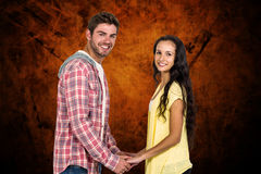 Composite image of smiling couple holding their hands and looking at camera Royalty Free Stock Photos