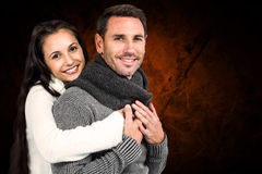 Composite image of smiling couple hugging and looking at camera. Smiling couple hugging and looking at camera against shades of brown Stock Images