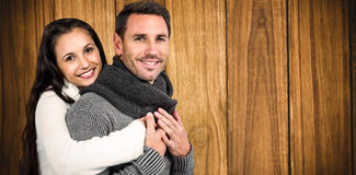 Composite image of smiling couple hugging and looking at camera. Smiling couple hugging and looking at camera against wooden background Royalty Free Stock Photos