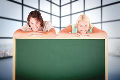 Composite image of smiling couple leaning on a whiteboard Stock Image