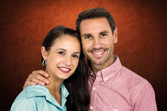 Composite image of smiling couple looking at camera. Smiling couple looking at camera against shades of brown Stock Photos