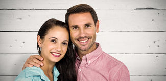 Composite image of smiling couple looking at camera. Smiling couple looking at camera against white wood Stock Photos
