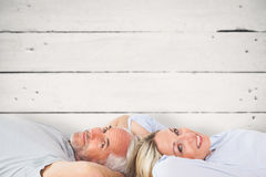 Composite image of smiling couple lying and looking at camera Royalty Free Stock Photography