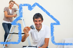 Composite image of smiling couple painting a wall Royalty Free Stock Photography