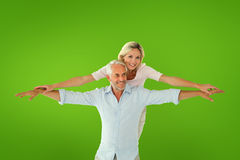 Composite image of smiling couple posing with arms out Royalty Free Stock Photos