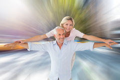 Composite image of smiling couple posing with arms out Stock Images