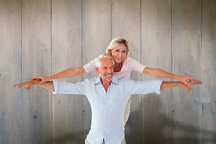 Composite image of smiling couple posing with arms out Stock Photos