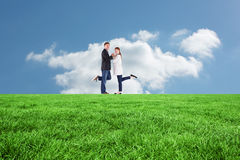 Composite image of smiling couple with raised legs Royalty Free Stock Image