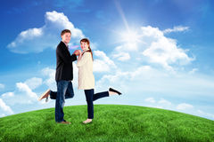 Composite image of smiling couple with raised legs Stock Image