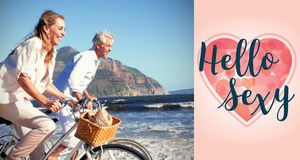 Composite image of smiling couple riding their bikes on the beach Royalty Free Stock Photography