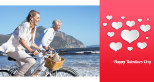 Composite image of smiling couple riding their bikes on the beach Royalty Free Stock Photos