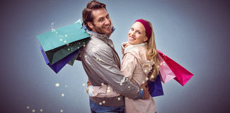 Composite image of smiling couple with shopping bags embracing Royalty Free Stock Images