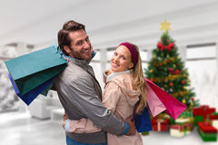 Composite image of smiling couple with shopping bags embracing Royalty Free Stock Photos