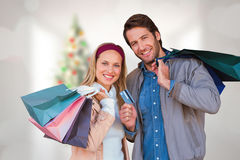 Composite image of smiling couple with shopping bags in front of window Stock Photos