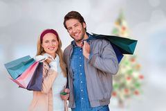 Composite image of smiling couple with shopping bags in front of window Stock Image