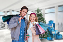 Composite image of smiling couple with shopping bags in front of window Royalty Free Stock Photo