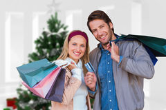 Composite image of smiling couple with shopping bags in front of window Royalty Free Stock Images