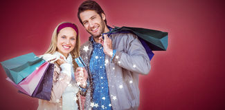 Composite image of smiling couple with shopping bags in front of window Stock Photo