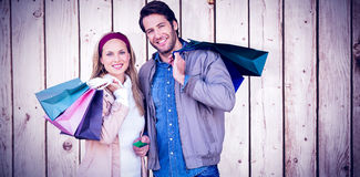 Composite image of smiling couple with shopping bags in front of window Royalty Free Stock Photography
