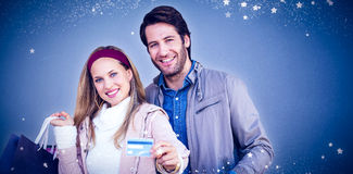 Composite image of smiling couple with shopping bags showing credit card Royalty Free Stock Photography