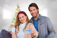 Composite image of smiling couple with shopping bags showing credit card. Smiling couple with shopping bags showing credit card against blurry christmas tree in Stock Photos