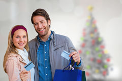 Composite image of smiling couple with shopping bags showing credit card Royalty Free Stock Image