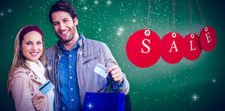 Composite image of smiling couple with shopping bags showing credit card. Smiling couple with shopping bags showing credit card against green Stock Image